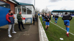Football and coronavirus: At Radcliffe, the game goes on… for now.  Rare game onging  While questionable playing surfaces are common at this time of year in the seventh tier — Radcliffe are 153 places behind Premier League leaders